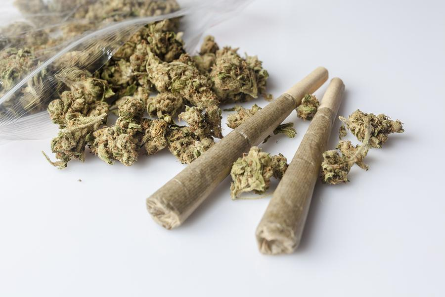 Pile+of+medical+cannabis+dried+buds+scattered+from+nylon+package+and+two+marijuana+joints+on+white+background+from+side