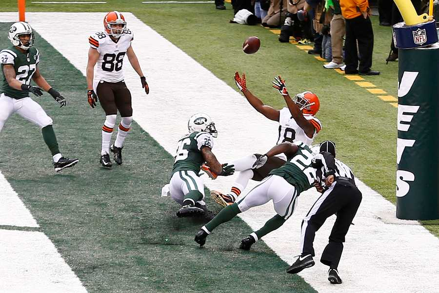 NEW YORK-DEC 22:  Cleveland Browns wide receiver Greg Little (18) leaps as New York Jets defensive back Aaron Berry (22) and safety Dawan Landry (26) defend during the first half at MetLife Stadium.
