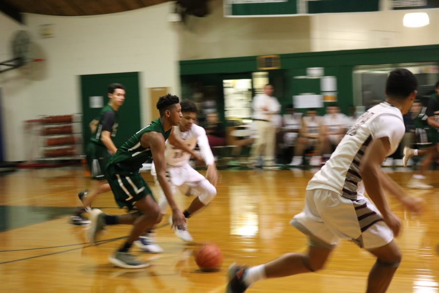 Gianni Thompson 21 dribbling up the court. Photo by Michelle Levinger 19.