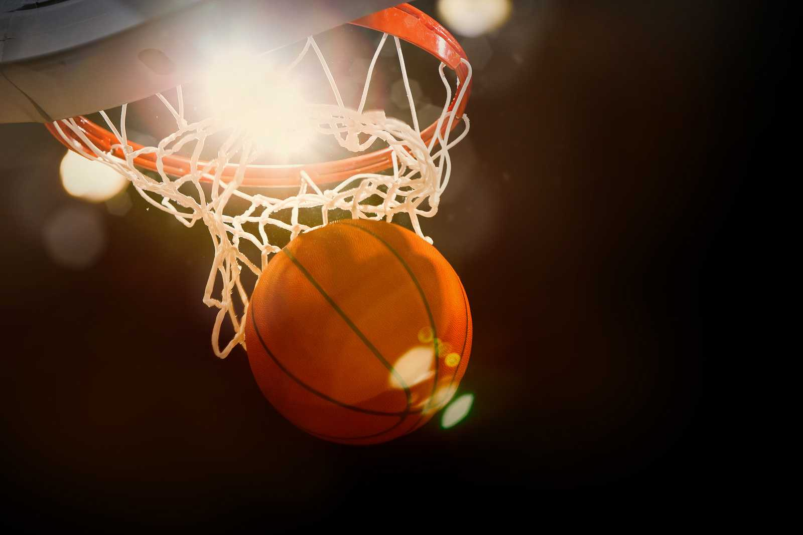 Basketball going through the basket at a sports arena (intention