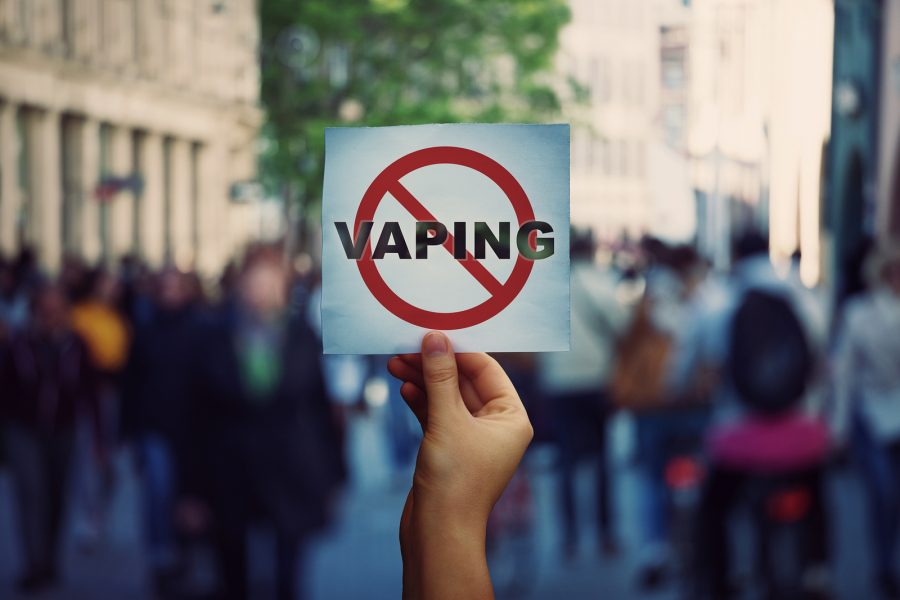 Human hand holding a protest banner stop vaping message over a crowded street background. Banning flavored vaping products to discourage people from smoking electronic cigarettes. Health risk concept.