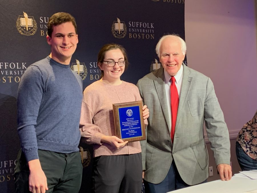 Greater Boston High School Newspaper Competition Director Richard Press presents Editors Miles Munkacy 20 and Caroline Champa  20 with the first place prize for excellence in online journalism.