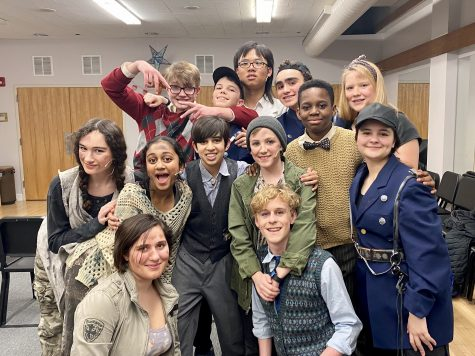 A group photo of several cast members as they prepare to perform.