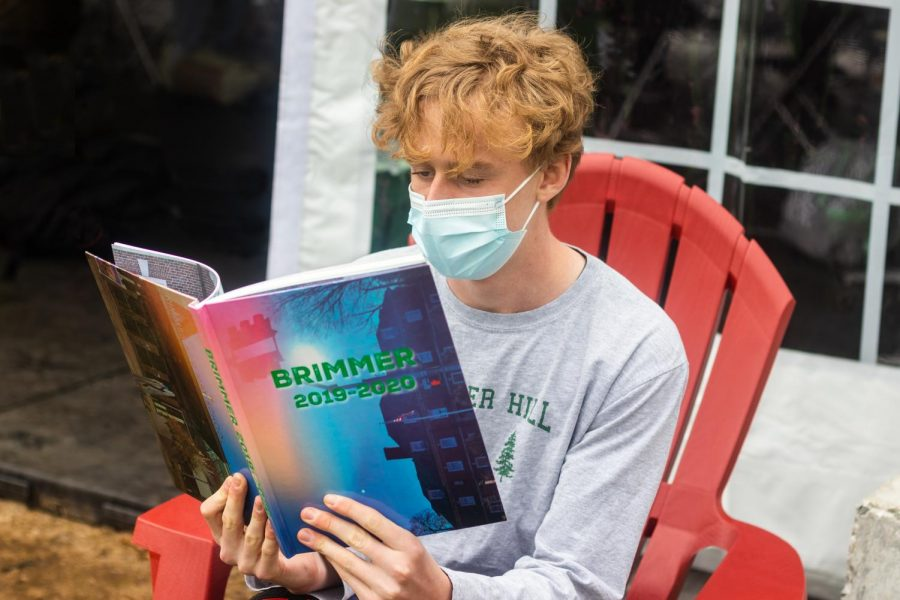 Brian Gamble 23 reads the 2019-2020 yearbook. Photo illustration by Edan Zinn 23.