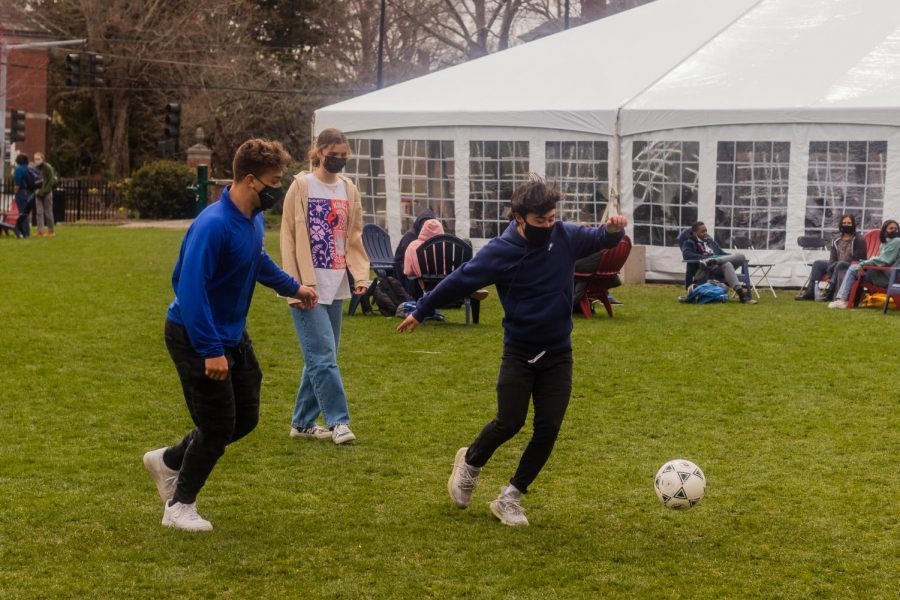 Brian Barrera 22, Owen Williams 23, and Leni Hicks-Dutt 23 play soccer at lunch.
