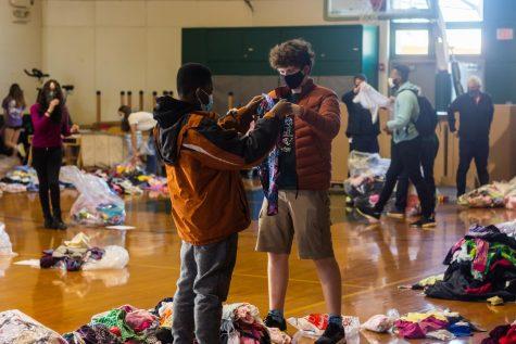 Ugo Adiele 23 and Kieran Cross 23 sort clothes for community service.