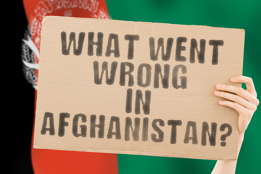 The question  What went wrong in Afghanistan?  on a banner in mens hand with blurred Afghan flag on the background. Purchased from BigStock.